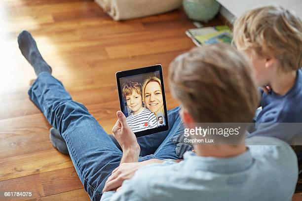Man and son sitting on floor talking to mother and brother on digital tablet video call