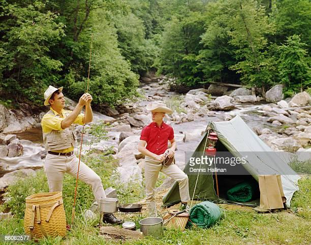 man and teenage boy camping by river shore - wildnis stock-fotos und bilder