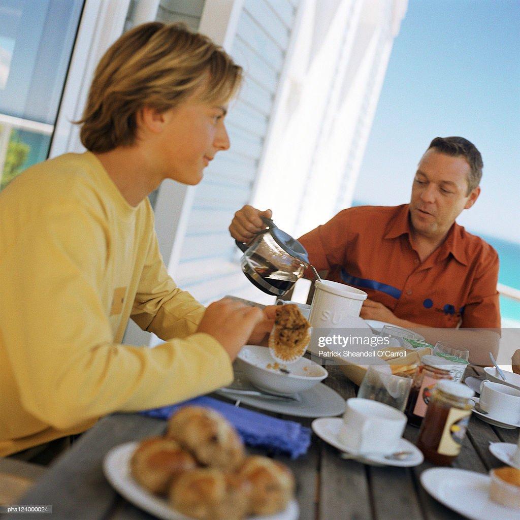 Man and teenage boy having breakfast outside : Stockfoto