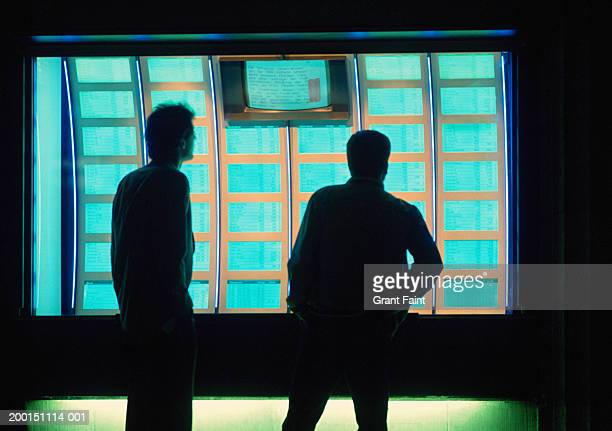 Man and teenage boy (15-17) looking at stock market displays, evening