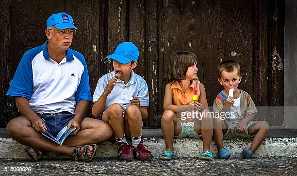 Man and three children eating lollipops