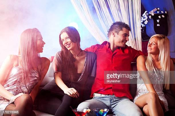 Mann, und drei Frauen reden in der disco.
