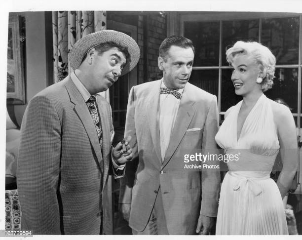 Man and Tom Ewell looking over at a smiling Marilyn Monroe in a scene from the film 'The Seven Year Itch', 1955.