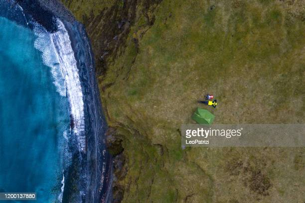 man and traveler exploring the rocky coastline - aerial view stock pictures, royalty-free photos & images