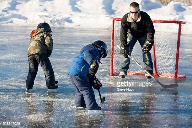 Man and two children playing hockey