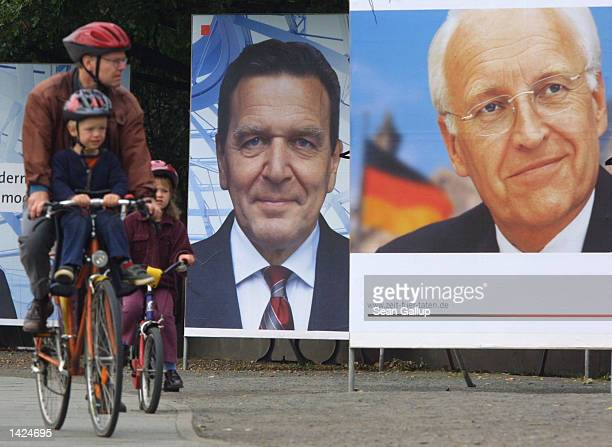 A man and two children ride past election billboards for German Chancellor Gerhard Schroeder and main opposition candidate Edmund Stoiber September...