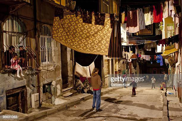 Man and two childs stitting in a window behind window grill watching other playing childs under close draped clotheslines in the district Tarlabasi...