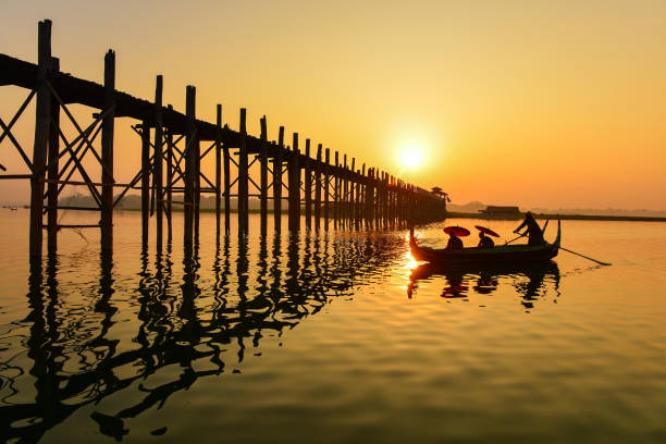 Man and two novice monks sailing near U Bein Bridge at sunrise, Mandalay, Myanmar