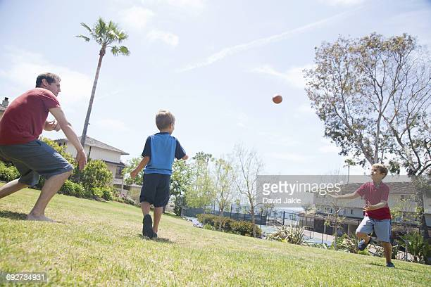 Man and two sons practicing American football in park