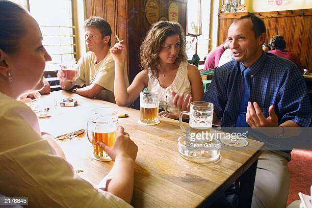 A man and two women chat over Pilsner Urquell beer at U Zlateho Tygra pub June 17 2003 in Prague Czech Republic U Zlateho Tygra is a haven for locals...