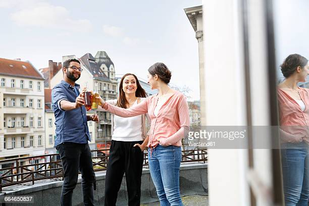 Man and two women clinking bottles on roof terrace