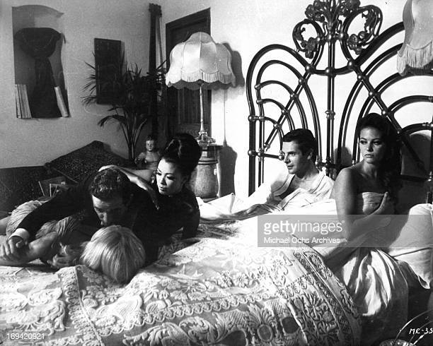 A man and two women fall into the bed of Philippe Nicaud and Claudia Cardinale in a scene from the film 'The Magnificent Cuckold' 1964
