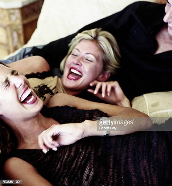 Man and two women laughing on bed, close-up