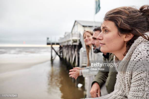 man and two women leaning on railing by the sea - travel stock-fotos und bilder