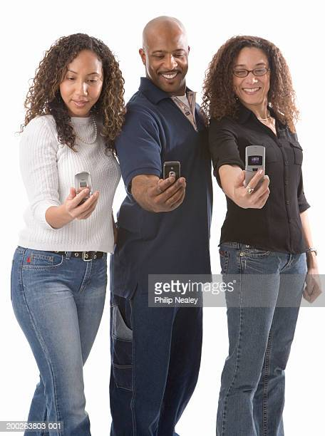 Man and two women looking at images on mobile phones