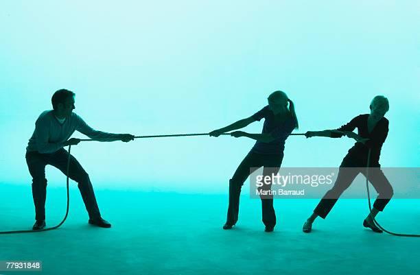 Mann und zwei Frauen spielen Tauziehen