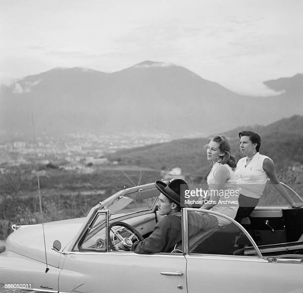A man and two women pose in a convertible car in Caracas Venezuela