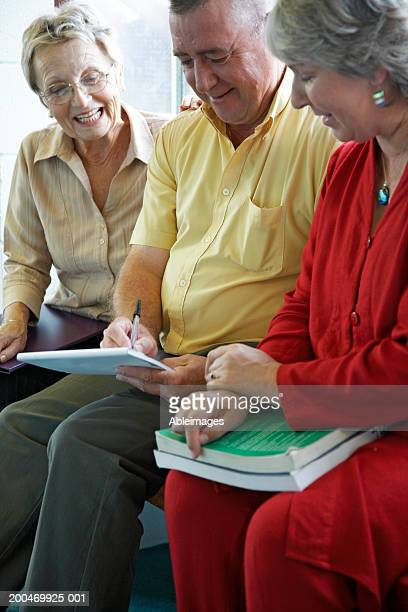 Man and two women sitting on bench in corridor, man writing notes