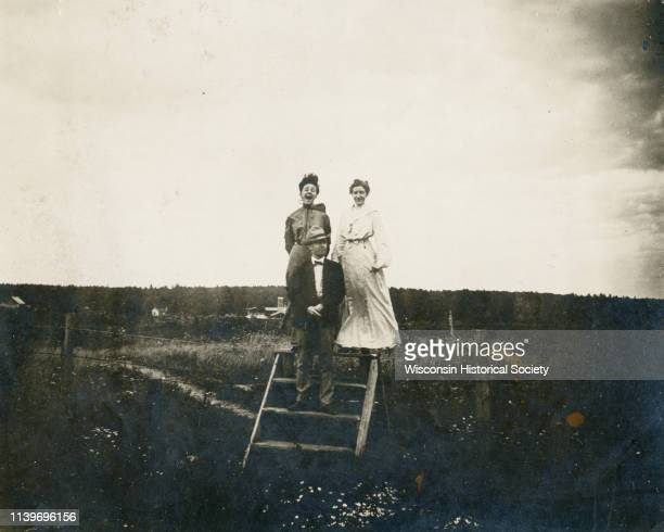 A man and two women standing on a stile of broad wood in the middle of a field Black River Falls Wisconsin 1899 The man standing on the second step...