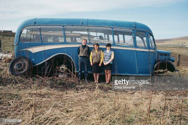 Man and two women, wearing Fair Isle knitwear, in front of a derelict bus, Shetland Islands, Scotland, June 1970.