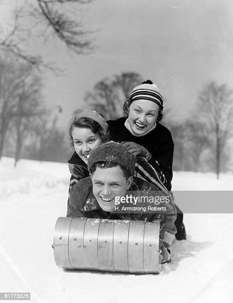 man and two women wearing wool hats and winter clothing tobogganing in snow with tree line in background front view of smiling faces fun. - tobogganing stock pictures, royalty-free photos & images