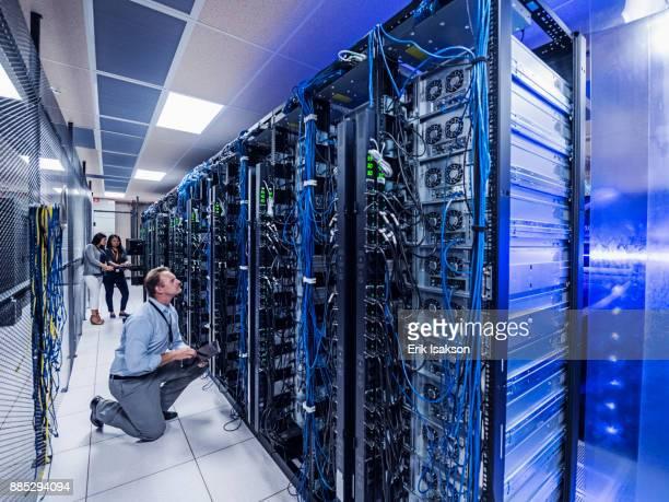 man and two women working in server room - data center stock-fotos und bilder