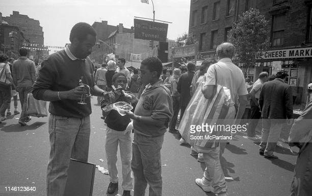 A man and two young boys share food with each other on 9th Avenue in Hell's Kitchen during the International Food Festival New York New York May 14...