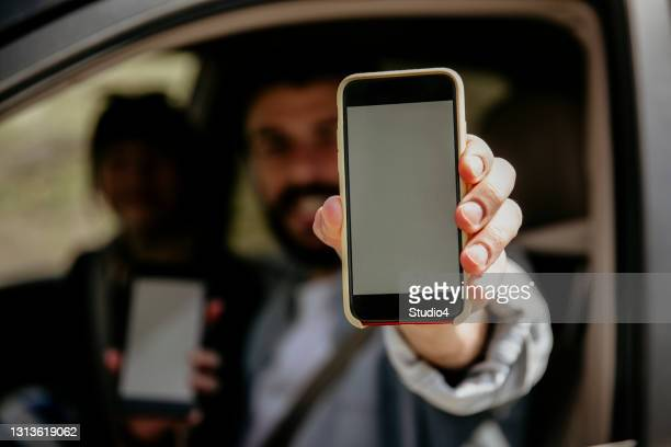 man and woman approaching mobile app - holding stock pictures, royalty-free photos & images