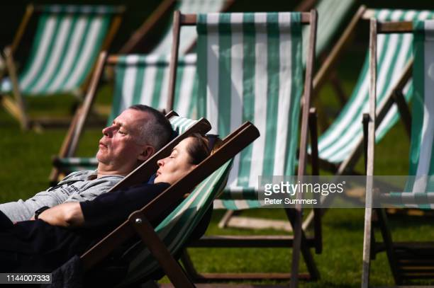 A man and woman are seen asleep in deck chairs while relaxing in the sunshine in St James's Park on May 15 2019 in London England Forecasters are...
