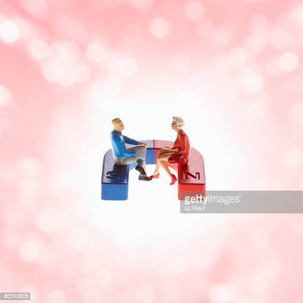 a man and woman are sitting on a magnet. - horseshoe magnet stock pictures, royalty-free photos & images