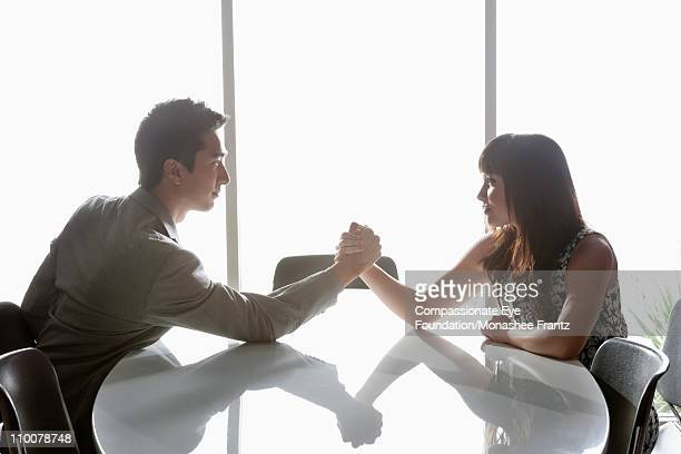 Man and woman arm wrestling at boardroom table.