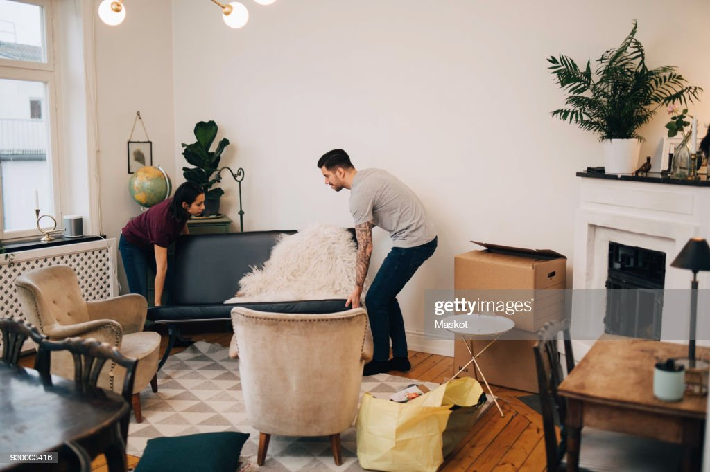 Man And Woman Arranging Sofa In Living Room High Res Stock Photo