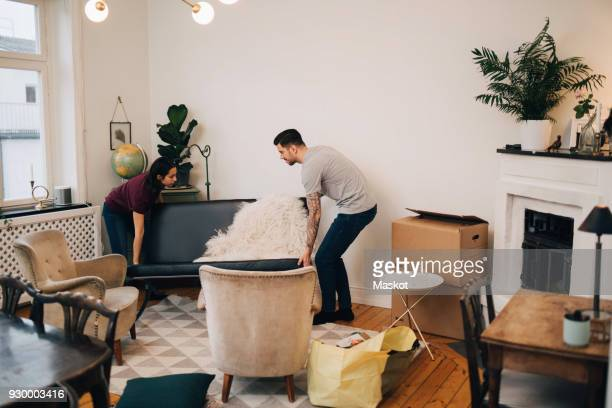 Man and woman arranging sofa in living room