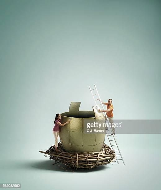 Man and woman assembling golden egg in nest