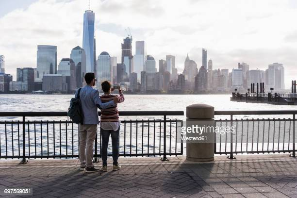 usa, man and woman at new jersey waterfront with view to manhattan - escapade urbaine photos et images de collection