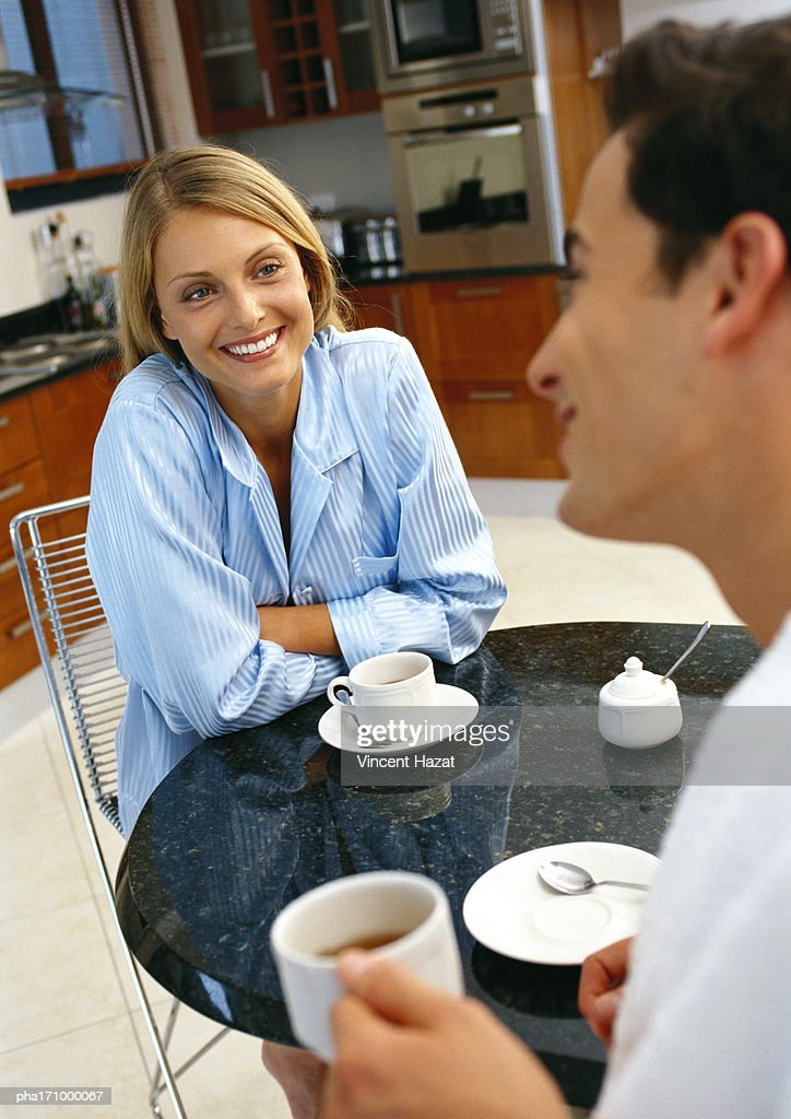 Man and woman at table with cups and saucers, rear view of man, blurred, focus on woman smiling in background : Stockfoto