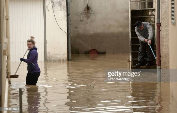 A man and woman attempt to clean following flood waters that swept through the streets following heavy rains in SaliesdeBearn south western France on...