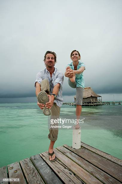 Man and woman attempting yoga pose on dock post.
