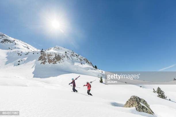 Man and woman backcountry skiers going up the mountain