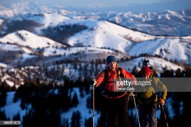 man and woman backcountry skiers reaching their summit in beautiful sunrise light. - park city stock pictures, royalty-free photos & images