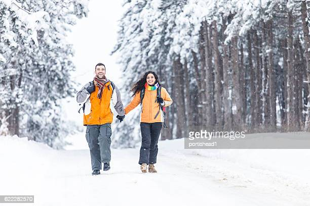 man and woman backpackers holding hands and walking in forest - heterosexual couple stock pictures, royalty-free photos & images
