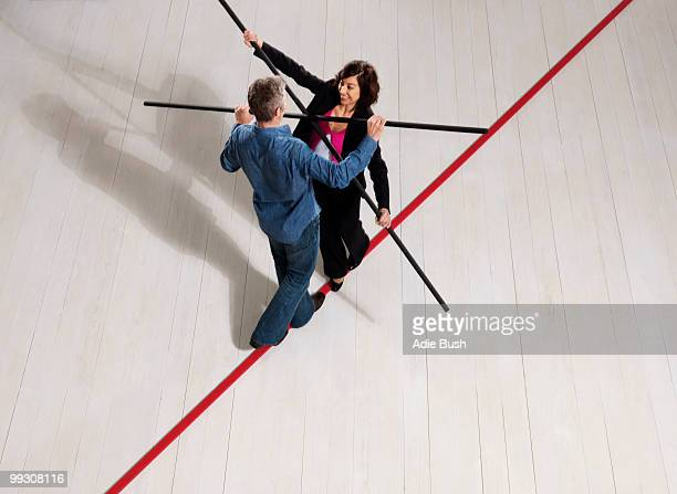 Man and woman balancing on thin red line