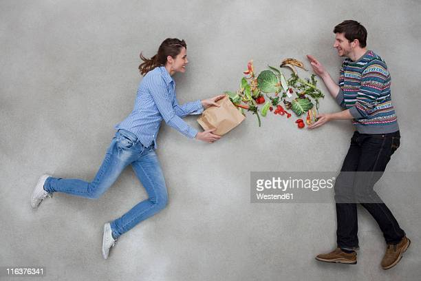 man and woman balancing vegetables - food contamination stock photos and pictures