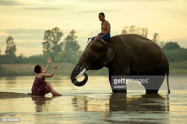 Man and woman bathing in river with elephant, Surin, thailand