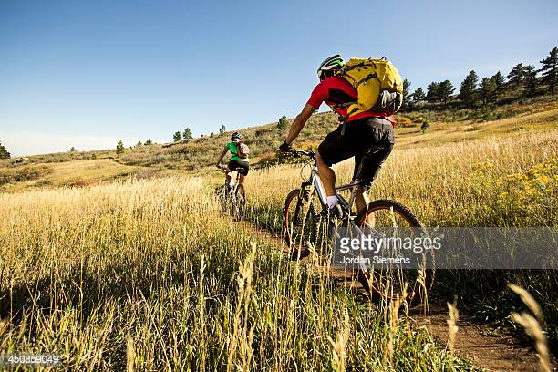 Man and woman biking on a dirt path.