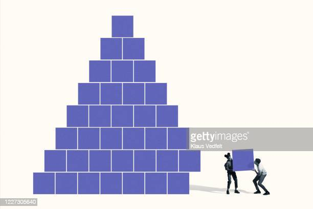 man and woman building pyramid with blue blocks - large stock pictures, royalty-free photos & images