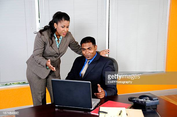 Man and Woman Business Partners Working  on  a Laptop