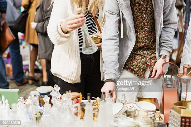 man and woman buying crockery at flea market - flea market stock pictures, royalty-free photos & images