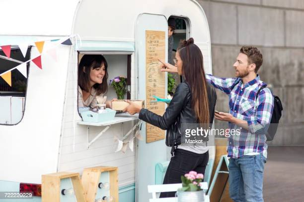 Man and woman buying food from saleswoman at food truck