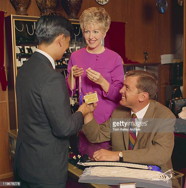 Man and woman buying pearl necklace in shop